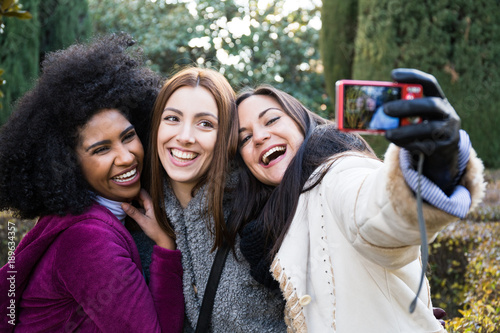 Three happy young pretty women taking selfie with casual camera in park in Madrid, Spain.