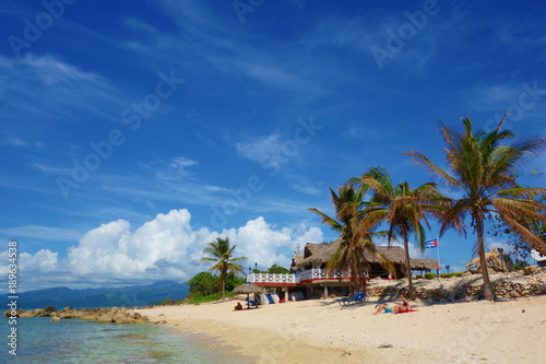 Foto op Aluminium Cathedral Cove Tropical sandy beach with Cuban flag and a traditional Cuban house surrounded by palm trees, Playa Ancon, Trinidad, Cuba, Caribbean Islands