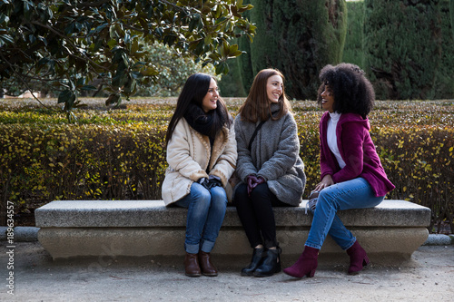 Three happy young multiethnic female friends sitting on park bench in Madrid, Spain.