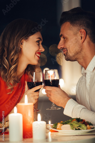 Young smiling lovers looking at each other and have romantic dinner with wine and food Fototapete