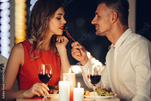 Smiling careful man feed his pretty girlfriend while have romantic dinner at home