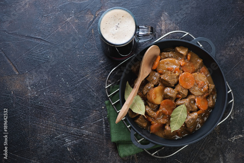 Cast-iron pan with Irish beef and beer stew and a mug of dark beer on a brown stone background, view from above with copyspace