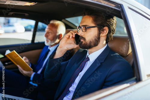 Senior businessman and his assistant sitting in limousine and working Tableau sur Toile