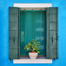 Italy, Venice, Burano Island. Traditional Colorful Walls And Windows With Opened  Shutters And Flowers In The Pot. Copy Space