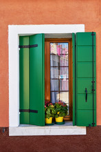 Italy, Venice, Burano Island. Traditional Colorful Walls And Windows With Bright Green Shutters And Flowers In The Pot.
