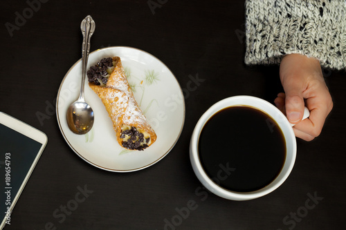 Fotografie, Obraz  Caucasian woman hand holds coffee cup with smartphone and italian cannoli on pla
