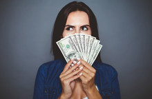 You Can Make Purchases. Beautiful Young Woman In Casual Clothes Joyfully Holding In Her Hand A Lot Of Dollars On A Gray Background Isolated. The Concept Of Money And Banking.