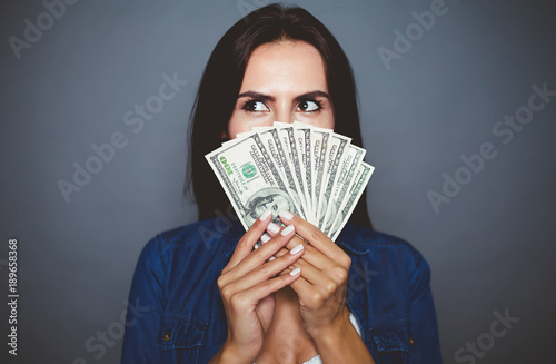 Fototapeta You can make purchases. Beautiful young woman in casual clothes joyfully holding in her hand a lot of dollars on a gray background isolated. The concept of money and banking. obraz