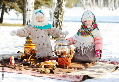 Fotografía  Two little girls in fur coats and shawls in Russian style on his head against the background of a samovar