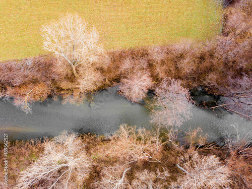 Wall Murals Vineyard Aerial view of a river surrounded by trees and colorful land , ladscape