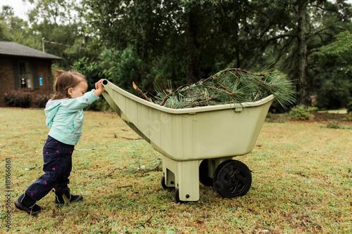 Zdjęcie XXL Mała dziewczynka pomaga czyścić w górę burzowych gruzów w jardzie