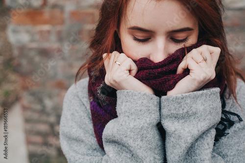 Fotografie, Obraz  красивая молодая девушка в пальто закуталась в шерстяной шарф beautiful young gi