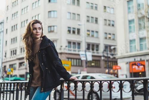 Pretty woman leaning on handrail in city