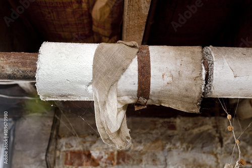 Photo Basement plumbing pipes wrapped with asbestos insulation.