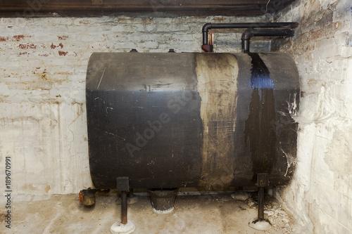 Fotografia  Old heating oil tank in dingy dank basement.