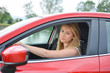 Frowning young blonde girl in red car