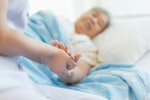 Nurse Sitting On A Hospital Be...