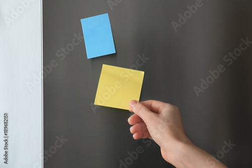 Woman touching paper sheet on refrigerator door