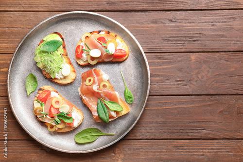 Fotografía  Tasty bruschettas with prosciutto and avocado on plate