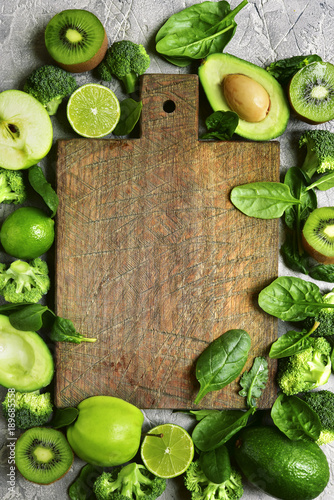 Variety of green fruits and vegetables with empty wooden cutting board .Top view with copy space. © lilechka75