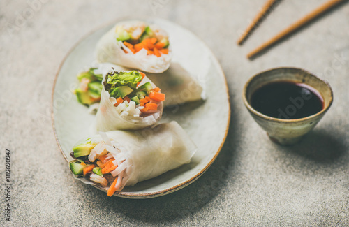 Shrimp and vegetable rice paper spring rolls with sauce and chopsticks on plate over grey background, selective focus. Asian cuisine, clean eating, vegetarian, dieting food concept