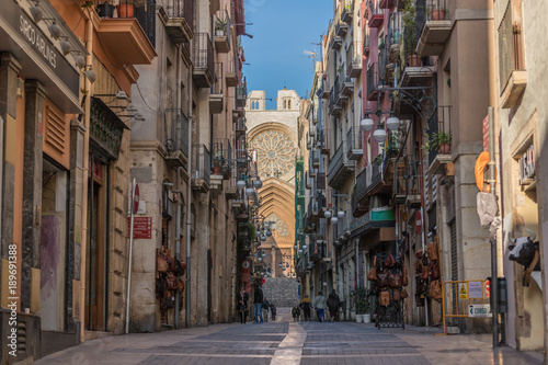 Cathedral of Tarragona at the end in the street in the middle of the trade of the old quarter of the Catalan city in Spain