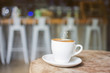 White cup of hot steaming coffee on an old log in the cafe with blurred coffee bar background
