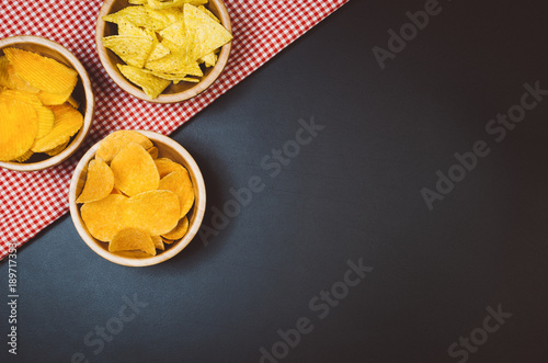 Party snacks - potato chips and snacks in bowl on black slate table Wallpaper Mural
