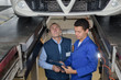apprentice mechanic repairing a car monitored by mentor