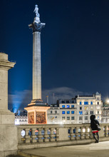 Night Shot Of Trafalgar Square With A Girl From The Back In The Foreground And Stars In The Sky, London.