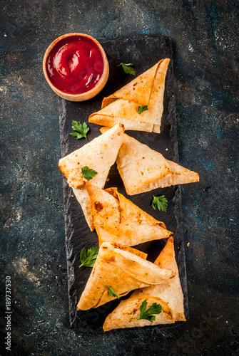 Asian food. Vegetarian samsa (samosas) with tomato sauce. Dark blue background copy space top view