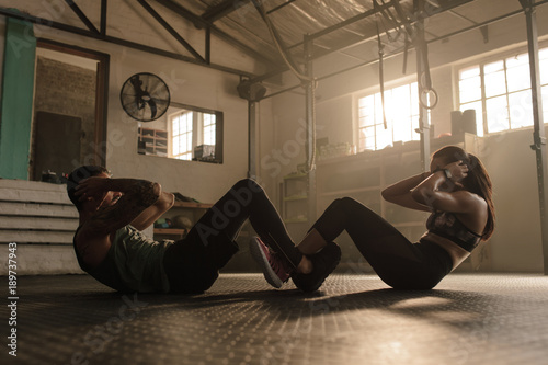 Poster Fitness Couple doing sit-ups together in gym