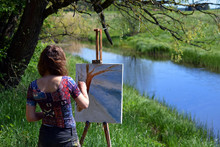 Female Artist Paints A Beautiful Small River Landscape On Canvas.