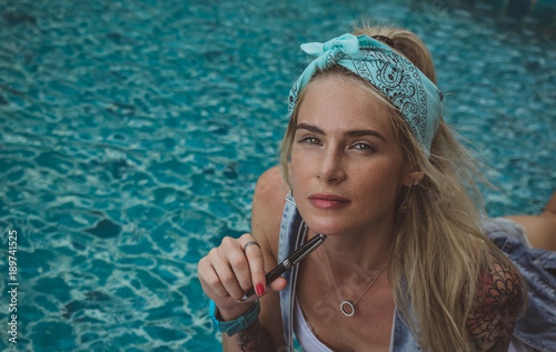 A beautiful college student at the pool performs homework Canvas Print