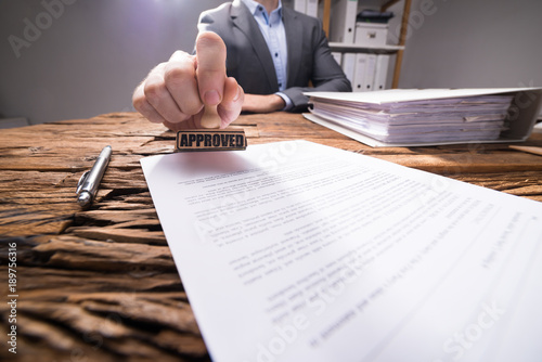 Photo Close-up Of A Businessperson Approving Document