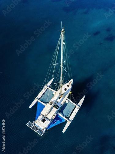 Fotografie, Obraz Aerial view of catamaran anchoring on coral reef.