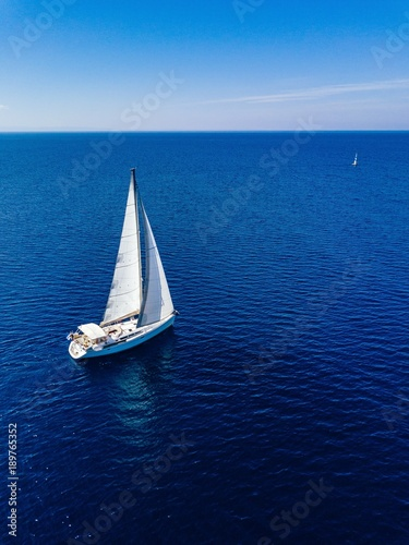 Aerial view from drone of white yacht in deep blue sea