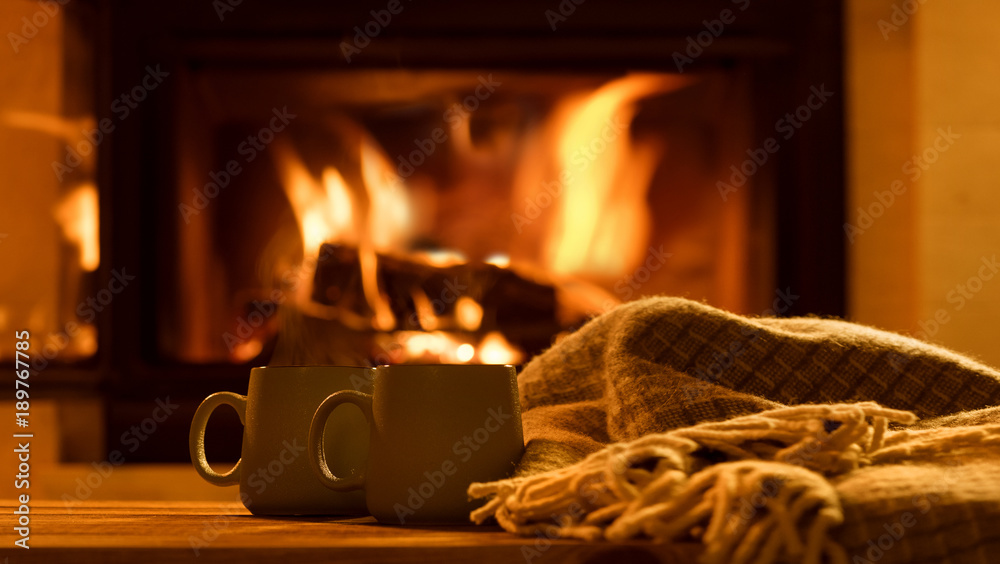 Fototapeta Steam from a cups with a hot cocoa on the fireplace background.