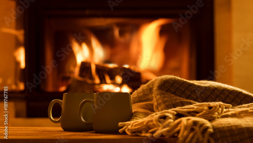 Steam from a cups with a hot cocoa on the fireplace background.
