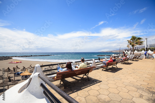 People sit on benches looking to beach in Las Americas, Tenerife, Canary Islands