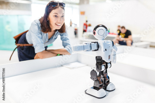 Foto A female student controls the work of an intelligent humanoid robot