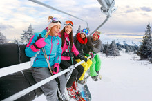 Cheerful Friends On Ski Lift Ride Up On Snowy Mountain