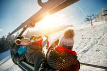 Friends Skiers And Snowboarders On Ski Lift In The Mountain At Winter Vacations
