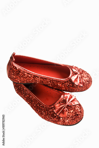 Fotografija  Pair of Red Glittered Shoes on a White Background