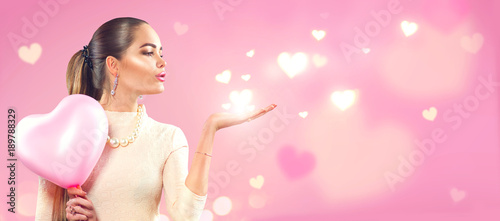 Valentine's day. Beauty girl with pink heart shaped air balloon pointing hand, blows hearts on pink background. Wide angle
