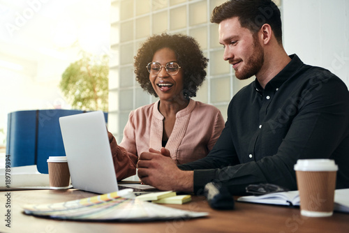 Photographie  Two smiling businesspeople sitting in an office using a laptop