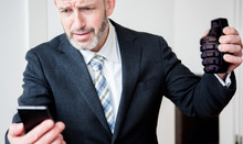 Upset Businessman Looking At Phone And Holding A Hand Grenade