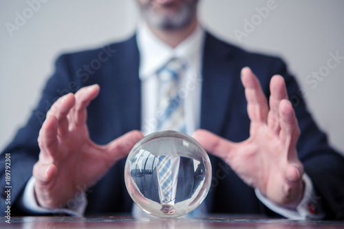 Photo businessman looking at glass ball on table