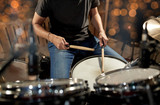 musician playing drum kit at concert over lights