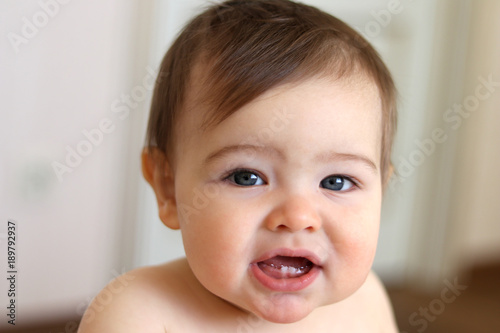 Little baby boy smiling with his first teeth, close-up